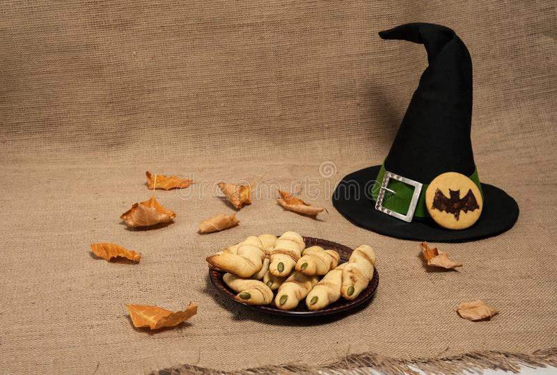 Terribly tasty cookies `Witch`s finger`, a pointed magic hat with a green ribbon and a silver buckle, autumn leaves on a textile. Homemade cakes for Halloween stock photos