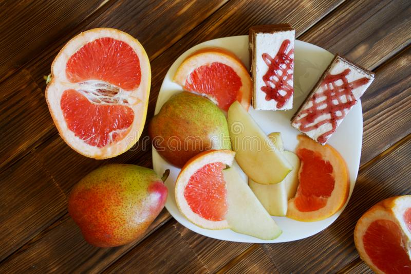 Homemade cakes, slices of grapefruit and pears lie in a white plate on a wooden table made of pine boards. Buffet in authentic royalty free stock photography