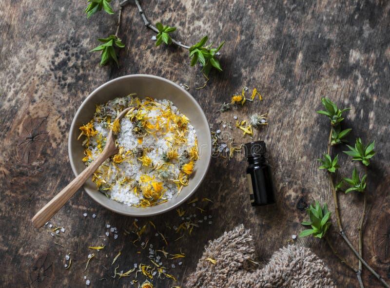 Homemade calendula, essential oil dead sea salt on wooden background stock photography