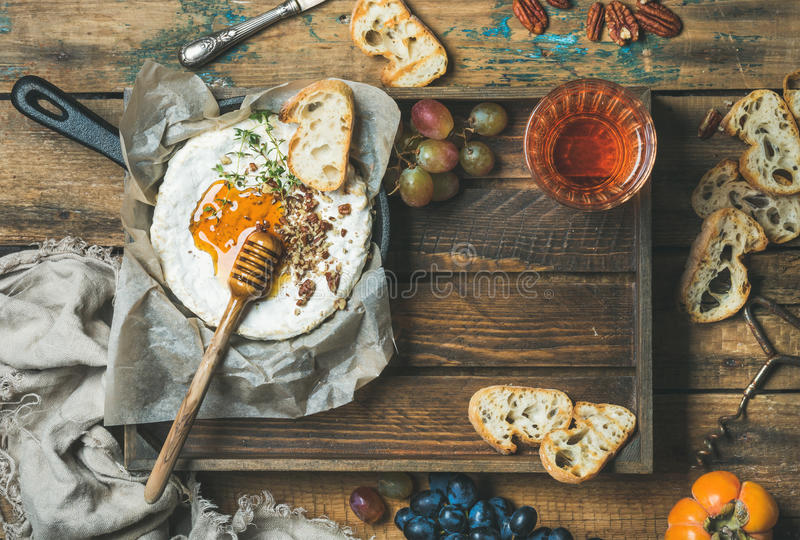 Homemade camembert with honey, glass of rose wine and baguette royalty free stock photos
