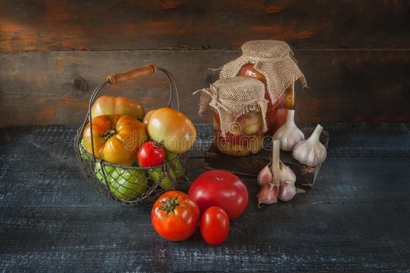 Homemade canned tomatoes in glass jars in a rustic style. The concept of growing, harvesting and preserving vegetables. stock image