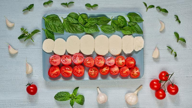 Homemade caprese salad with organic ingredients: mozzarella cheese, cherry tomatoes, fresh basil leaves, garlic. Italian food. Homemade caprese salad with stock photo