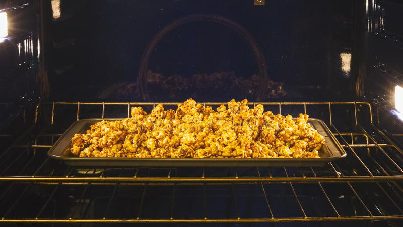 Homemade caramel corn finished baking in the oven. Fresh and tasty caramel corn coming out of the oven royalty free stock images