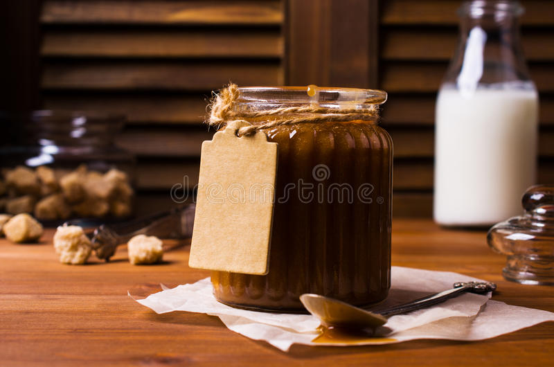 Homemade caramel sauce. In the glass on a wooden background. Selective focus royalty free stock photo