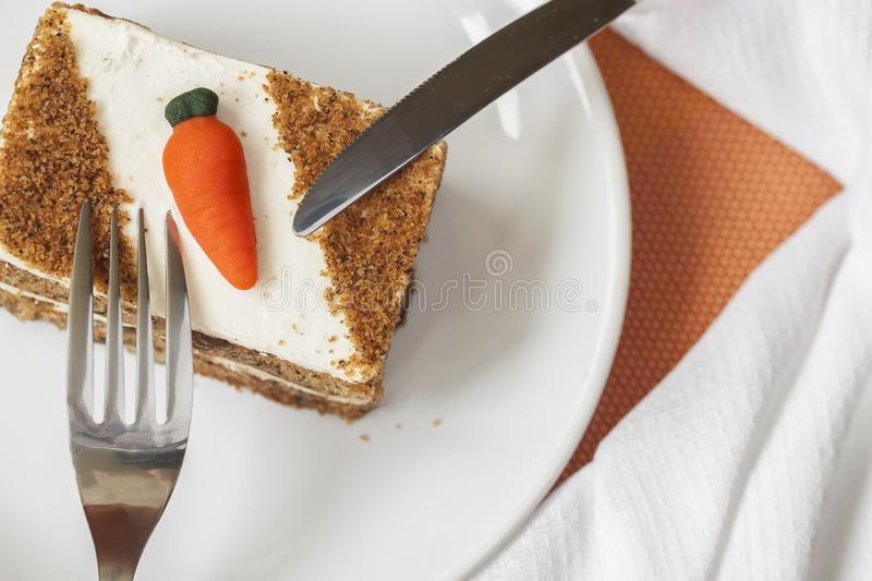 Homemade carrot cake with carrot decorations on white plate, fork, knife, napkin, top view. royalty free stock photos