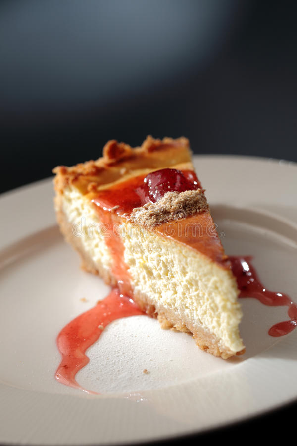 Homemade Cheese Cake. A piece of homemade cheese cake with strawberry jam served in a plate stock image