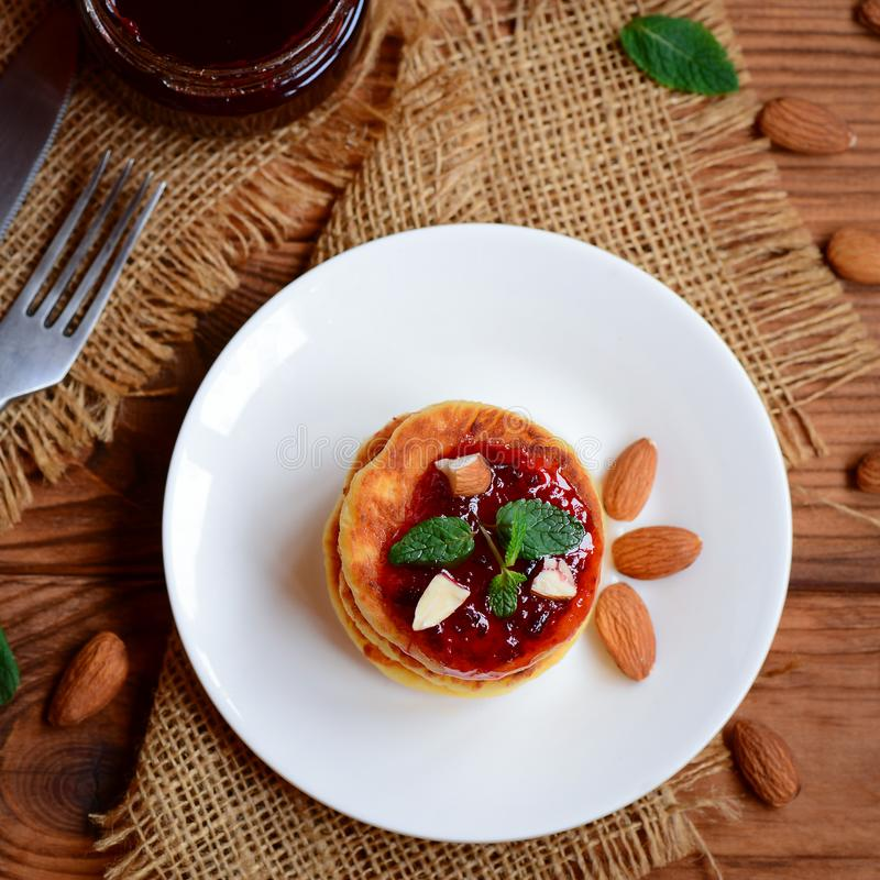 Tasty homemade cottage cheese pancakes. Easy cottage cheese pancakes with berry jam and nuts. Top view royalty free stock photo