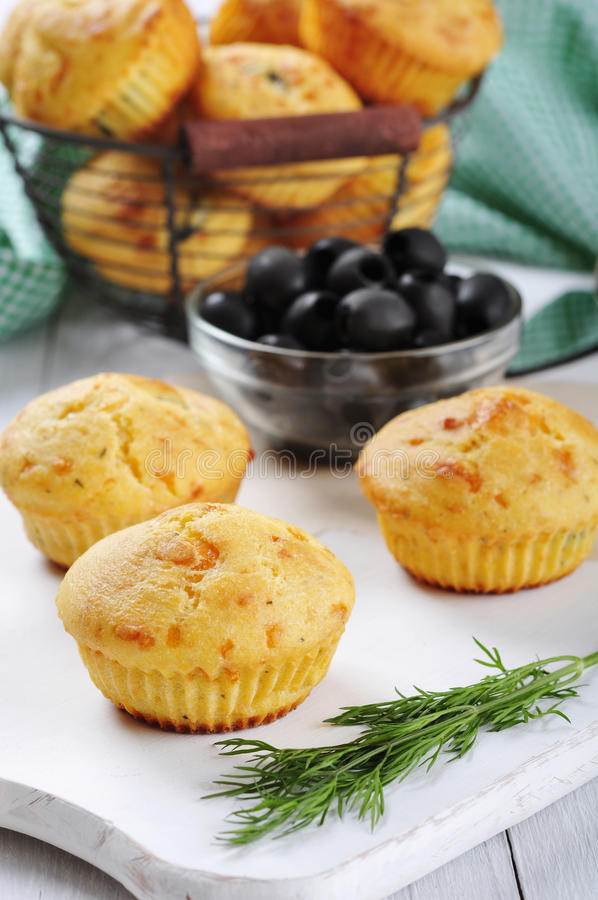 Homemade cheese muffins. With olives and herbs on white wooden background royalty free stock image