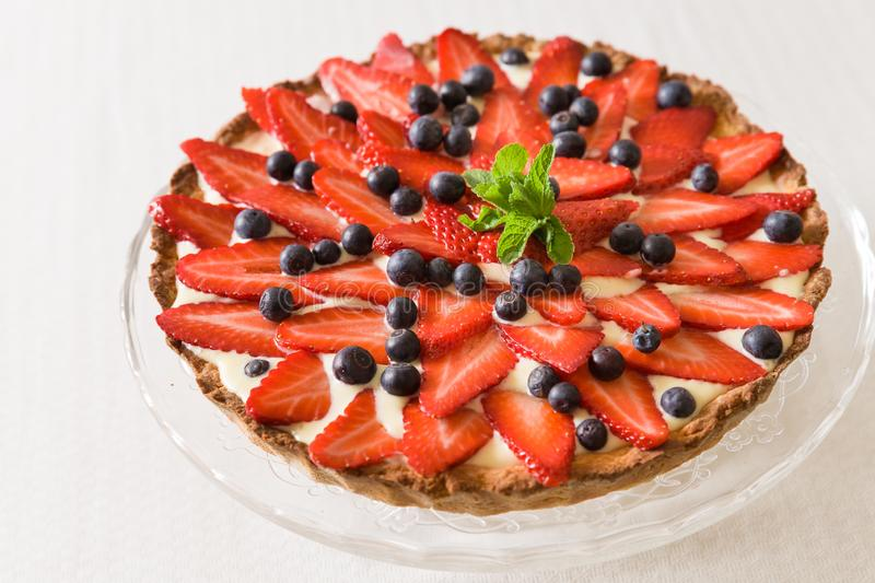 Homemade cheesecake decorated with organic strawberries, blueberries and fresh mint and cream. Nice pie for a holiday royalty free stock image