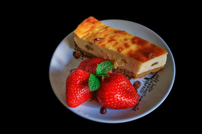 Homemade cheesecake on a plate decorated with fresh strawberries and mint leaves royalty free stock images