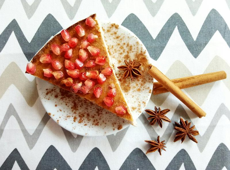 Homemade cheesecake with pomegranate and cinnamon sticks and anis stars. Homemade cheeesecake with pomegranate seeds and cinnamon sticks and anis stars royalty free stock images