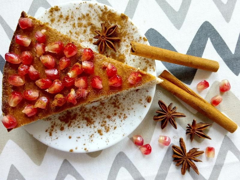 Homemade cheesecake with pomegranate and cinnamon sticks and anis stars. Homemade cheeesecake with pomegranate seeds and cinnamon sticks and anis stars stock image