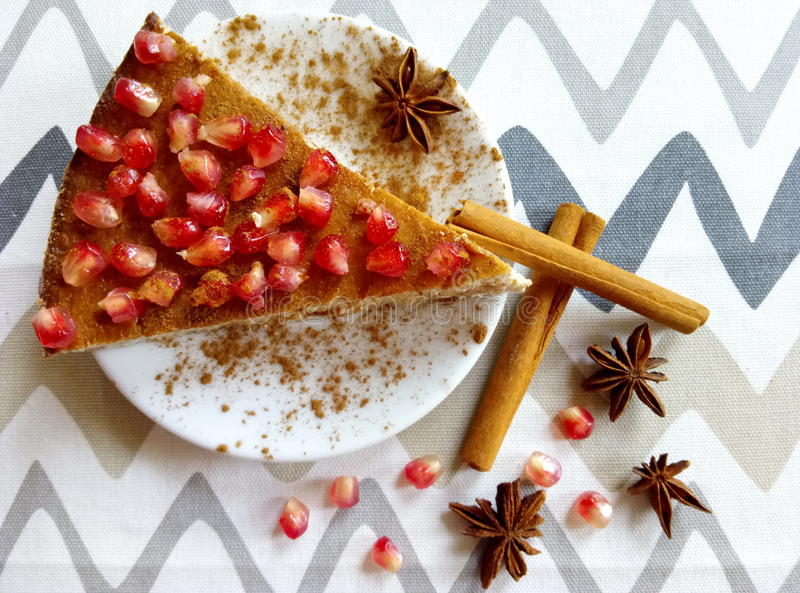 Homemade cheesecake with pomegranate and cinnamon sticks and anis stars. Homemade cheeesecake with pomegranate seeds and cinnamon sticks and anis stars stock images