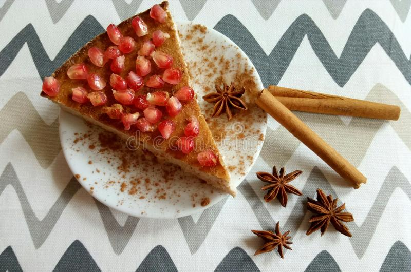 Homemade cheesecake with pomegranate and cinnamon sticks and anis stars. Homemade cheeesecake with pomegranate seeds and cinnamon sticks and anis stars royalty free stock photography