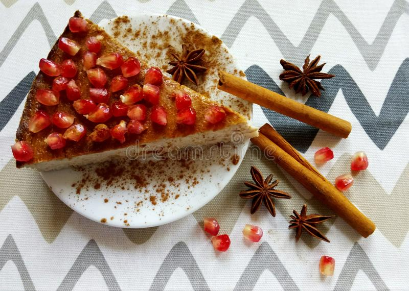 Homemade cheesecake with pomegranate and cinnamon sticks and anis stars. Homemade cheeesecake with pomegranate seeds and cinnamon sticks and anis stars royalty free stock photos