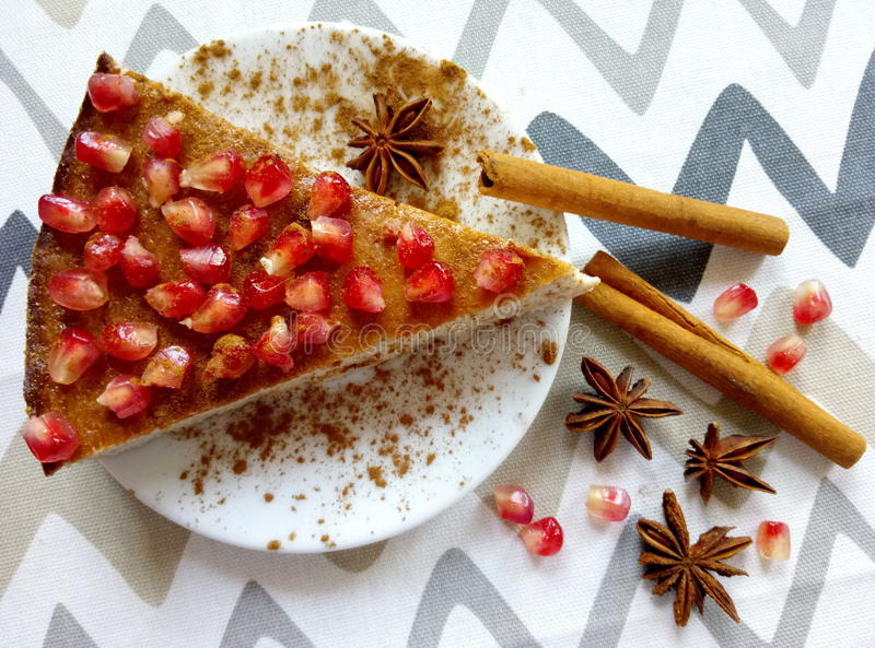 Homemade cheesecake with pomegranate and cinnamon sticks and anis stars. Homemade cheeesecake with pomegranate seeds and cinnamon sticks and anis stars stock photos