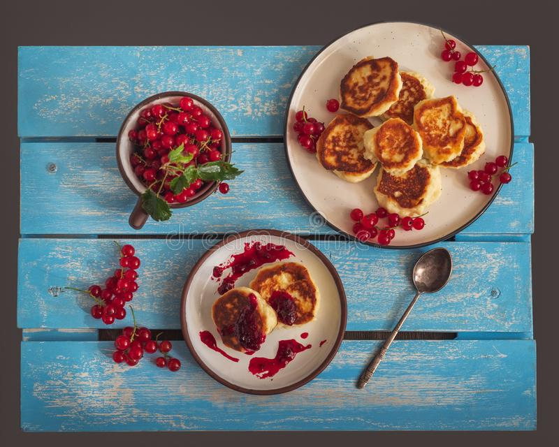 Homemade cheesecakes on two plates with jam and sprigs of red currant, a mug with currant royalty free stock images
