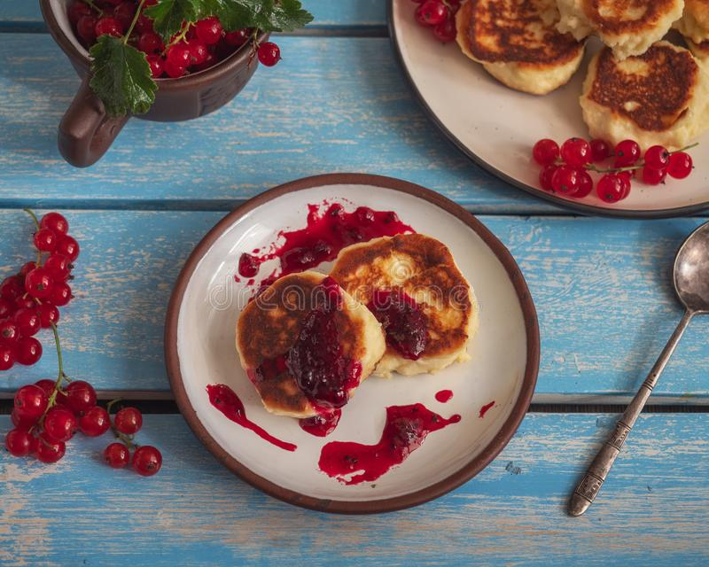 Homemade cheesecakes on two plates with jam and sprigs of red currant stock photos