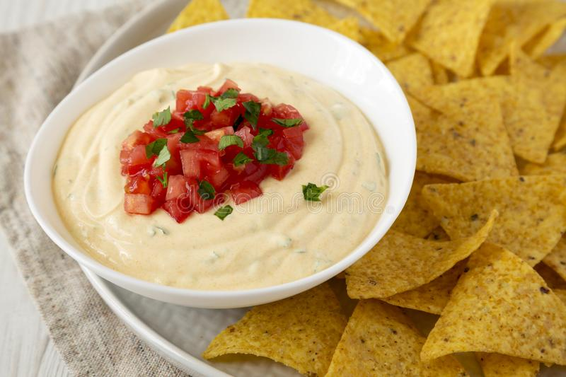 Homemade cheesy dip in a bowl, yellow tortilla chips, side view. Close-up stock photo
