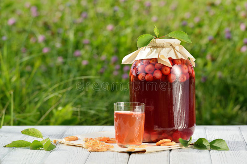 Homemade cherry preserved canned compote in glass with cookies on white wooden table in garden stock photos