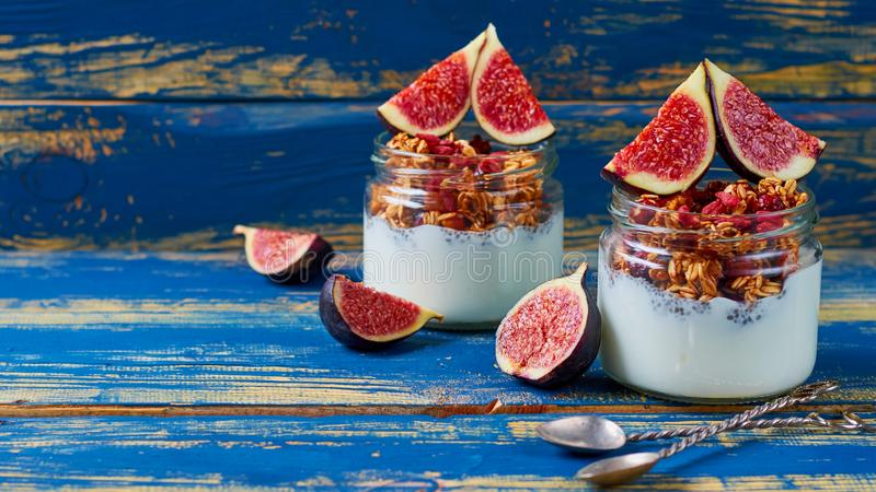 Homemade chia milk pudding with granola and fresh figs in the glass jars on the blue kitchen table. Detox superfoods breakfast. Homemade chia milk pudding with royalty free stock photos