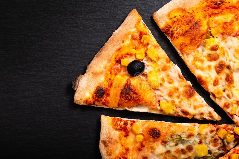 Homemade Chicken curry,black olive and corns Pizza on black slat royalty free stock photo