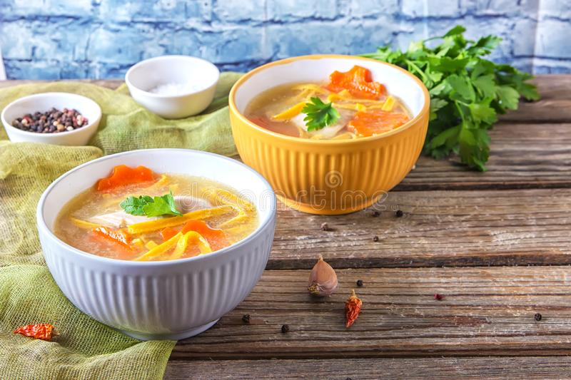 Homemade chicken soup with noodles and vegetables in metal pan on wooden table.  stock image