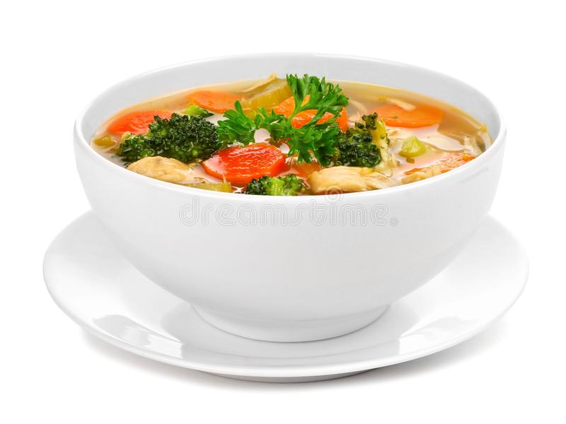 Homemade chicken vegetable soup isolated on white. Homemade chicken vegetable soup in a white bowl with saucer. Side view isolated on a white background royalty free stock photo