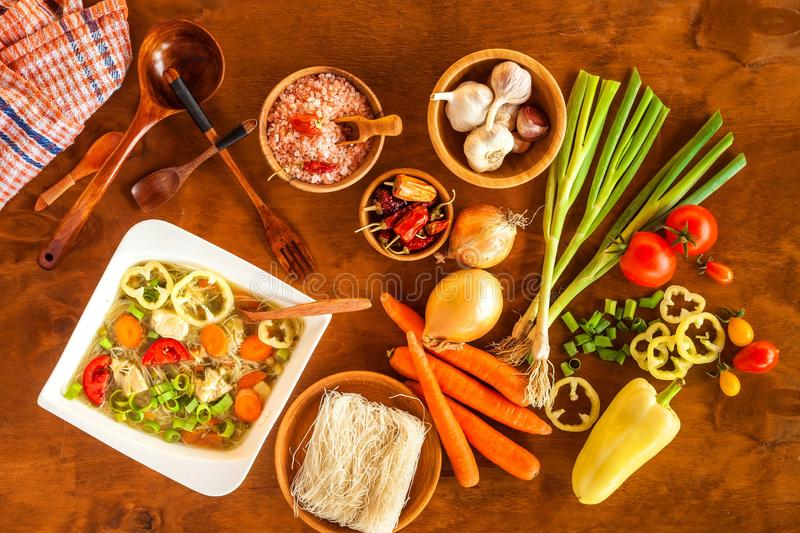 Homemade chicken vegetable soup, overhead view. Chicken soup with rice noodles. Fresh vegetables for soup. Diet food royalty free stock images