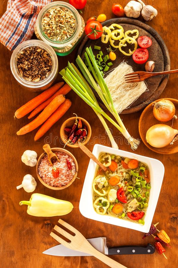 Homemade chicken vegetable soup, overhead view. Chicken soup with rice noodles. Fresh vegetables for soup. Diet food.  stock photos