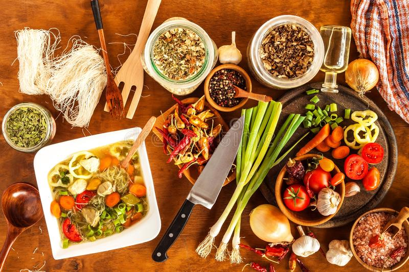Homemade chicken vegetable soup, overhead view. Chicken soup with rice noodles. Fresh vegetables for soup. Diet food.  stock images
