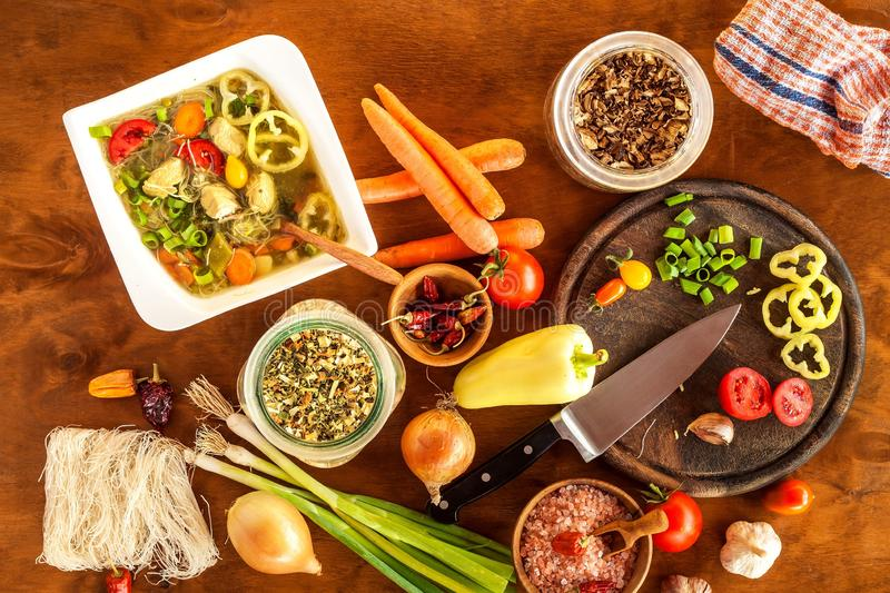 Homemade chicken vegetable soup, overhead view. Chicken soup with rice noodles. Fresh vegetables for soup. Diet food.  royalty free stock image