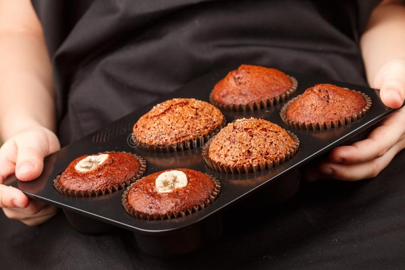 Homemade chocolate, banana and caramel muffins in a baking dish in the children`s hands royalty free stock photos