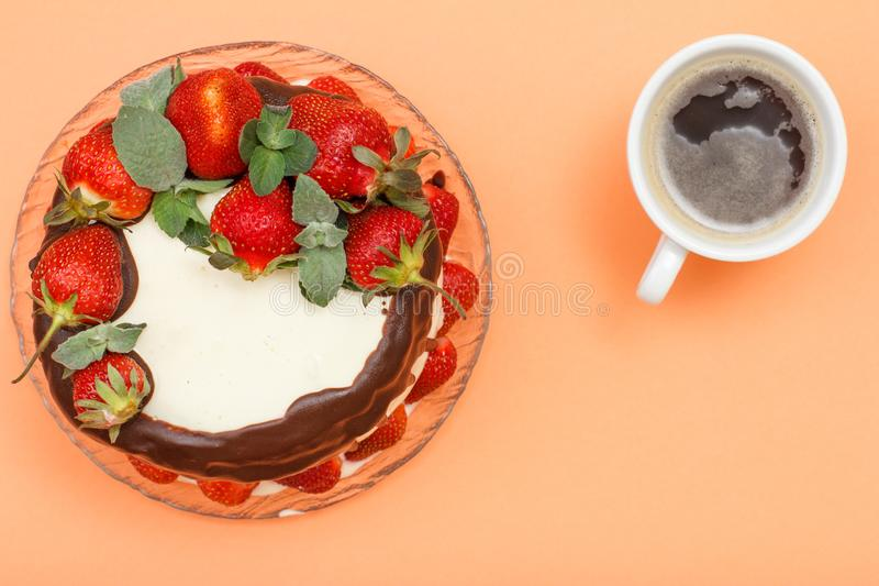Homemade chocolate cake decorated with fresh strawberries on glass plate and cup of coffee stock images