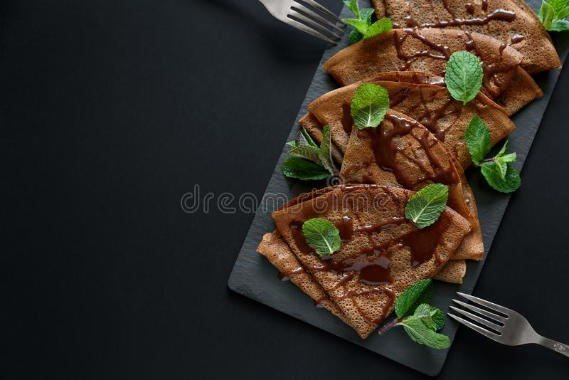 Homemade chocolate crepes served with blueberries, sauce and mint leaves on slate plate. Selective focus. Top view. Copy space royalty free stock photo