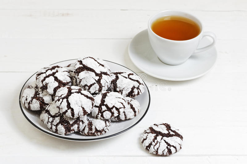 Homemade chocolate crinkles cookies powdered sugar. And cup of tea on white wooden table stock photography