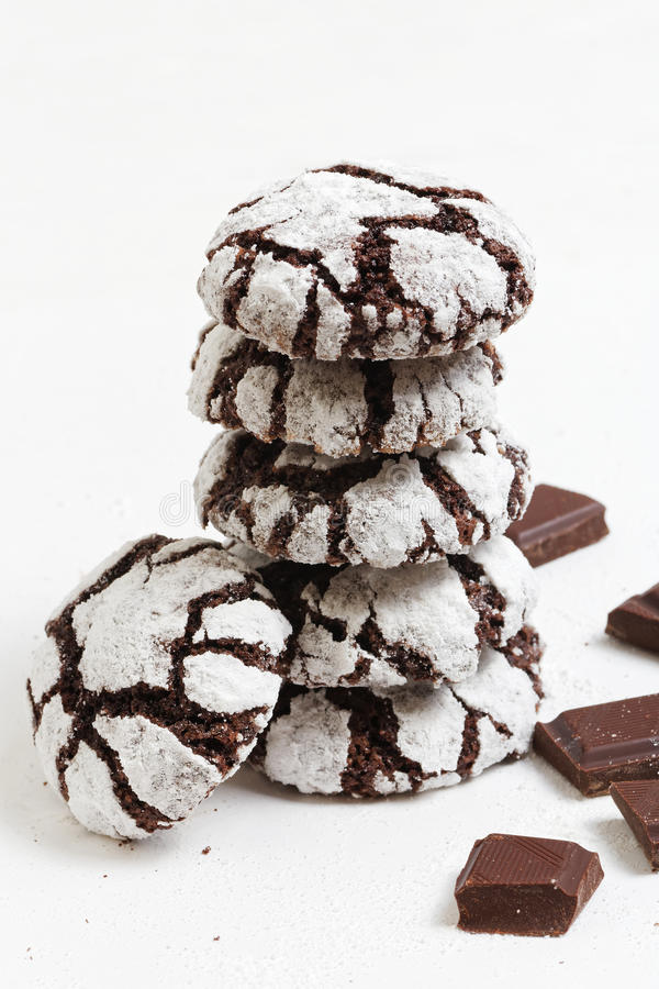 Homemade chocolate crinkles cookies powdered sugar. Stacked homemade chocolate crinkles cookies powdered sugar and pieces of chocolate on white background stock photography
