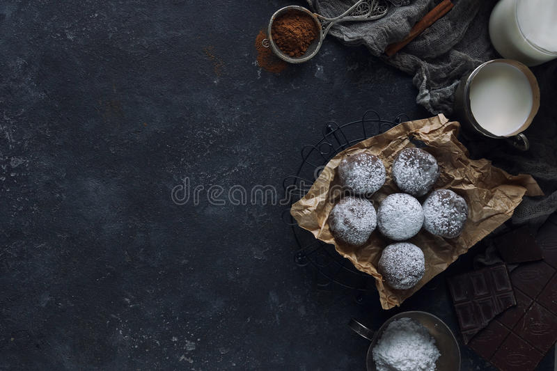 Homemade chocolate crinkles in powdered sugar, chocolate cookies with cracks and a glass of milk royalty free stock images