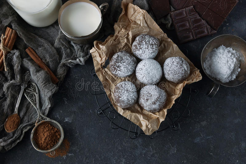 Homemade chocolate crinkles in powdered sugar, chocolate cookies with cracks and a glass of milk. Homemade chocolate crinkles in powdered sugar on vintage plate royalty free stock photography