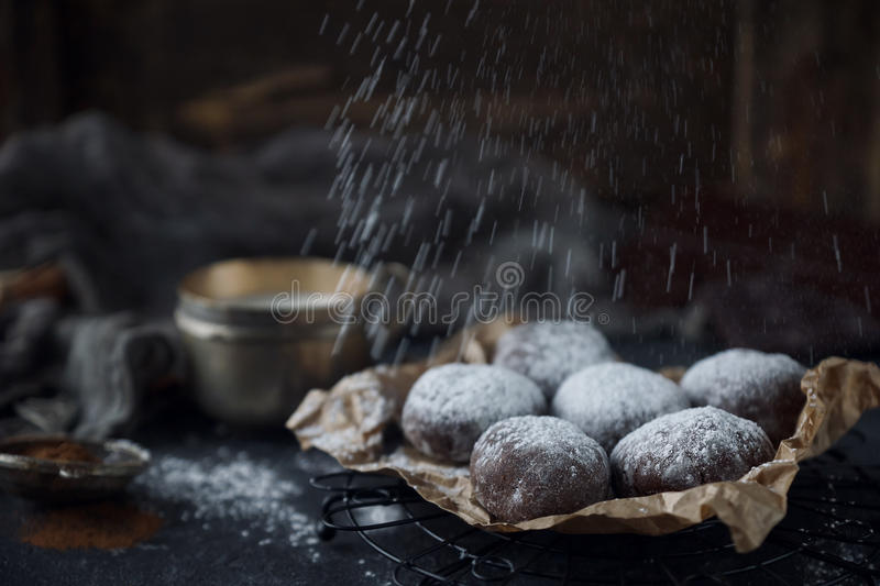 Homemade chocolate crinkles in powdered sugar, chocolate cookies with cracks and a glass of milk. Homemade chocolate crinkles in powdered sugar on vintage plate stock image