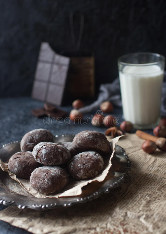 Homemade chocolate crinkles in powdered sugar, chocolate cookies with cracks and a glass of milk. Homemade chocolate crinkles in powdered sugar on vintage plate stock photography