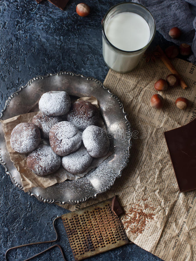 Homemade chocolate crinkles in powdered sugar, chocolate cookies with cracks and a glass of milk. Homemade chocolate crinkles in powdered sugar on vintage plate royalty free stock image