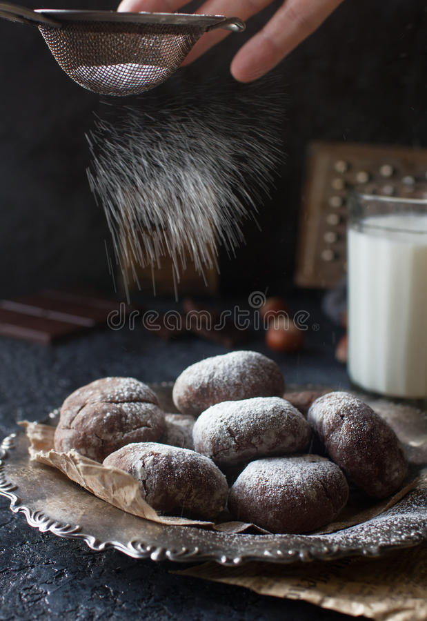 Homemade chocolate crinkles in powdered sugar, chocolate cookies with cracks and a glass of milk. Homemade chocolate crinkles in powdered sugar on vintage plate royalty free stock photo