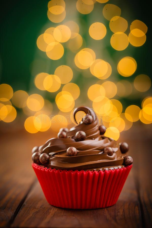 Chocolate christmas cupcake with bokeh on background. Homemade chocolate cupcake with chocolate chips in red cup on wooden background with garland lights bokeh royalty free stock image