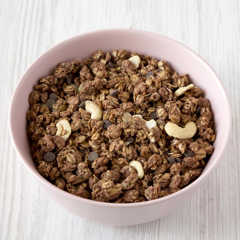 Homemade chocolate granola with nuts in a pink bowl over white wooden surface, low angle view. Closeup.  royalty free stock image
