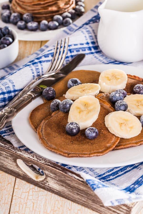 Homemade chocolate pancakes with berries and banana stock photos