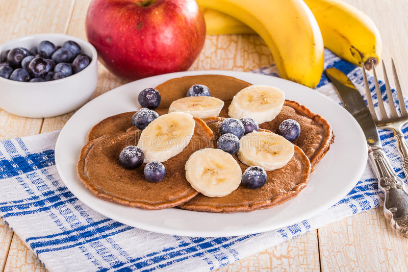 Homemade chocolate pancakes with berries and banana royalty free stock photography