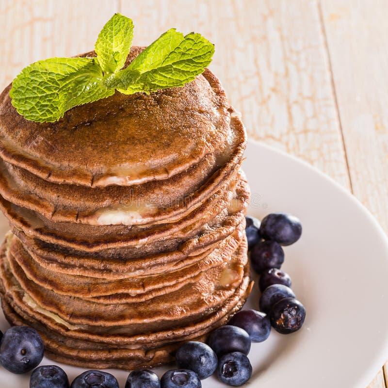 Homemade chocolate pancakes with berries stock photo