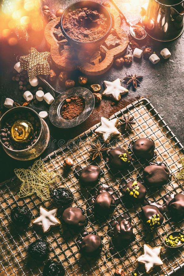 Homemade chocolate praline on dark rustic table with cacao powder , nuts, marshmallows and cinnamon star Christmas cookies. Home stock photography