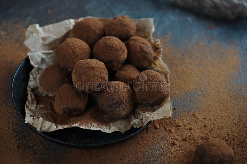 Homemade chocolate truffle candies with cocoa powder on craft paper, sweet dessert stock images